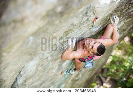 Young male rock climber on challenging route gripping small handholds. View from above.