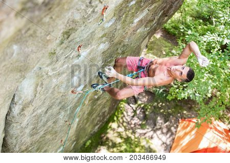 Young man falling off vertical cliff while lead climbing view from above