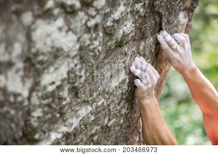Rock climber's hands gripping small holds on natural cliff