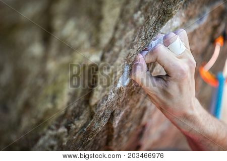 Rock climber's hand gripping small hold on natural cliff closeup view