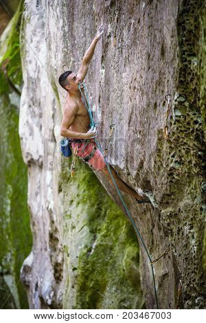 Rock climber holding rope with teeth before making clip on natural cliff