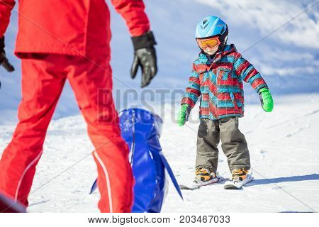Young skier sliding down towards towards toy penguin and ski instructor. Ski lesson in alpine school.
