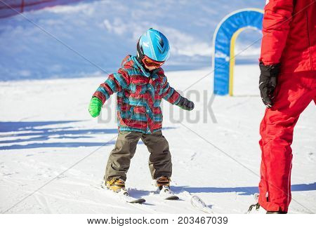 Young skier and ski instructor on in beginners' area. Ski lesson in alpine school.