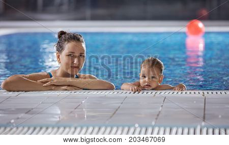Young woman and little son resting poolside and looking at camera