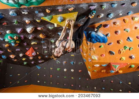Young woman bouldering in climbing gym looking at camera while hanging upside down
