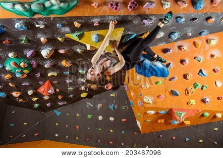 Expressive young woman bouldering in climbing gym struggling to solve challenging problem