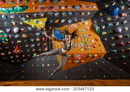 Expressive young woman falling down while bouldering in indoor climbing gym