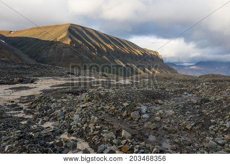 Meltwater in glacier moraine creating Longyearbyen river in Svalbard. Beautifully carved mountain in evening sunlight in background.