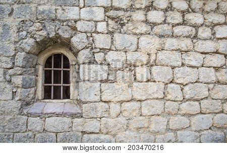 window with a bar in the old church. Masonry walls.