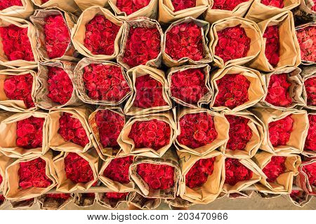 Top view of several bouquets of red roses on sale inside Bangkok flower market Thailand