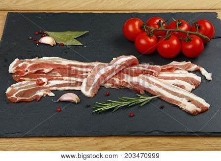 Raw Bacon Slices, Spice And Tomato On Black Board