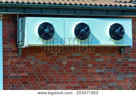 Compressor of an air conditioning mounted on a house wall.