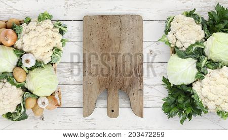 Healthy eating concept wooden cutting board with basket vegetables cabbage and cauliflower on kitchen white worktop copy space top view