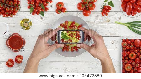 hands taking photo of food with the smartphone from above saucepan and tomatoes sauce on kitchen white wooden worktop copy space top view