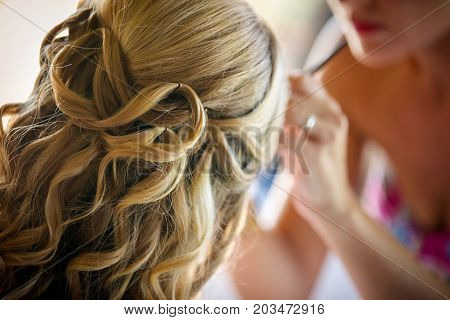 Makeup artist / hair stylist preparing styling a young blond girl.
