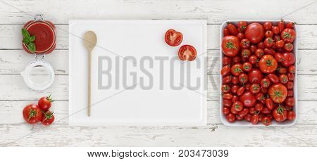 tomato sauce above cutting board with spoon glass jar and tomatoes isolated on white wooden kitchen worktop background copy space top view