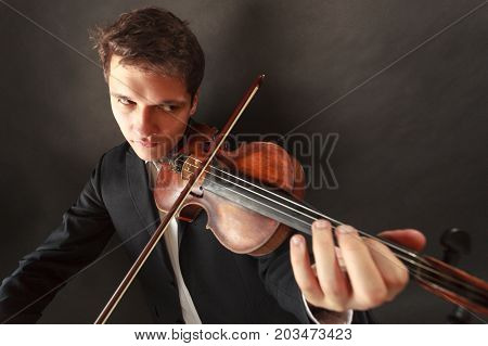 Music passion hobby concept. Young man man dressed elegantly playing emotionally on wooden violin. Studio shot on dark background