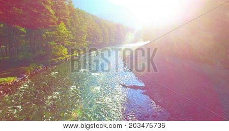Aerial UHD 4K view. Mid-air flight over fresh and clean mountain river at sunny summer morning. Green trees and sun rays on horizon. Direct on sun