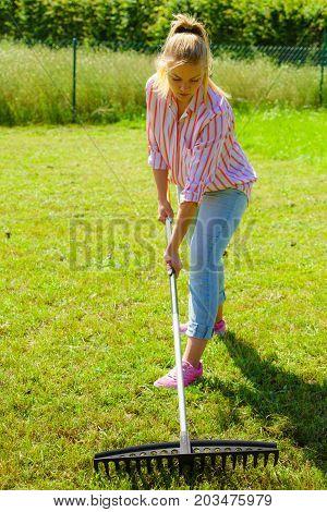 Woman Using Rake To Clean Up Garden