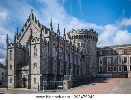 Dublin Ireland - August 7 2017: Original church and tower of The Castle build with dark gray stones under blue sky with white clouds. Newer side building in back.
