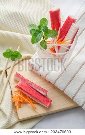 Crab stick with sliced carrot and radish in a glass on fabric background.