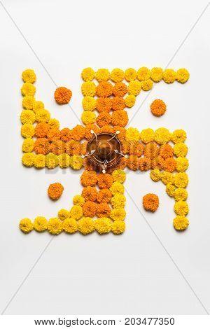 stock photo of hindu auspicious symbol called Swastika or swastik made using marigold flower/zendu/genda phool & diwali diya / clay lamp, Flower rangoli in the shape of Swastika for diwali/pongal/onam