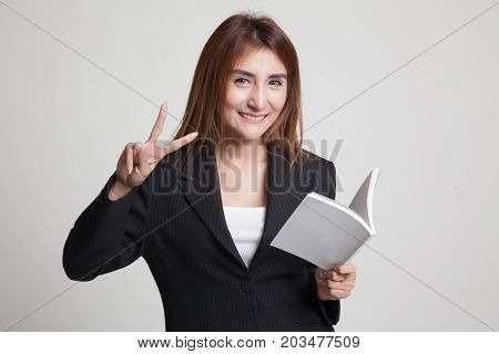 Young Asian Woman Show Victor Sign With A Book.