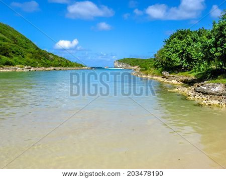 The famous landmark of Plage de la Porte d'Enfer north of Grande-Terre in Guadeloupe. A beach and a lagoon protected by the rushing ocean waves by a coral reef at the entrance of the gorge.