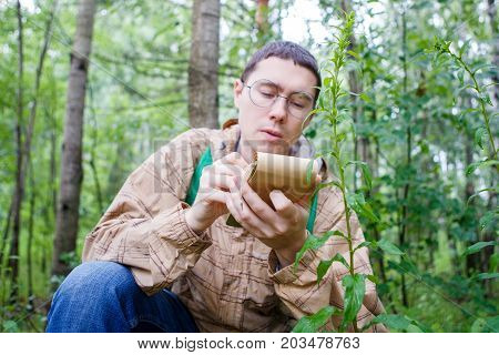Photo of dark-haired biologist in glasses writes in notebook in forest among plants and trees in summer afternoon
