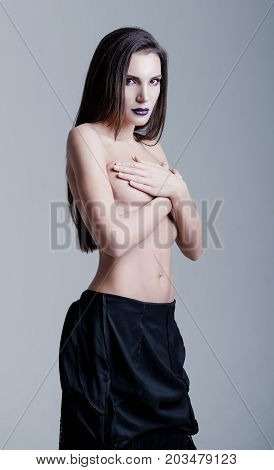 Studio portrait of a beautiful sexy young girl. Topless