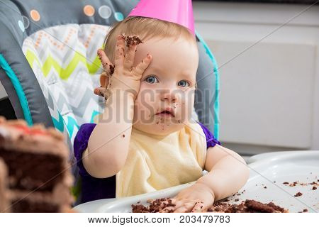 A little girl first birthday. She has forgotten something