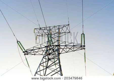 The tip end anchor metal supports of overhead power lines costs with wires and bundles of strands of high-voltage insulators against the clear blue sky