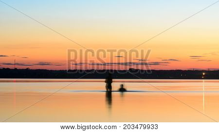 Two dark silhouette in the water at night on the background of the bright sunset and the coast of the village with the forest and lights floating on the quiet surface men, and the shivering girls.