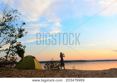 Wide girl in yoga pants and a hat outdoors on a sandy beach by the river and tourist tents by the tree and bushes taking pictures on the phone beautiful sunset sky with clouds.