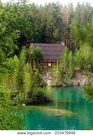 Wooden house with a satellite dish standing in the woods in the pine trees on the shores of stone lake with the island and turquoise water.