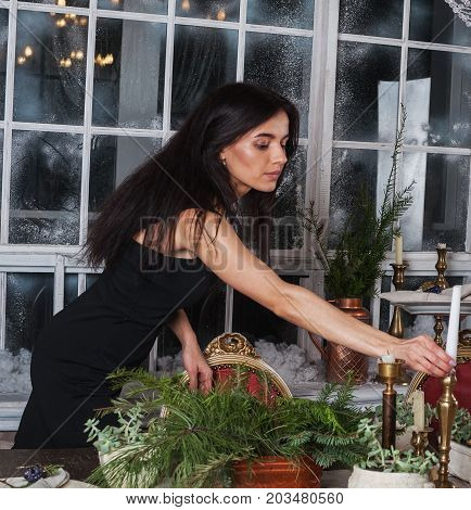Beautiful girl decorate table for Christmas and evergreen centerpiece.