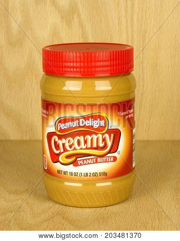 RIVER FALLS,WISCONSIN-SEPTEMBER 09,2017: A jar of Peanut Delight brand creamy peanut butter with a wood background.
