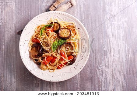 Vegetable (aubergine courgette pepper) pasta on plate viewed from above