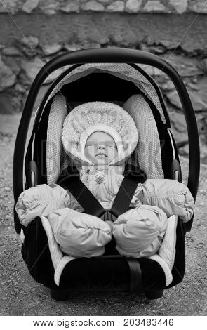 newborn boy sleeping in the car seat outdoors ( black and white )