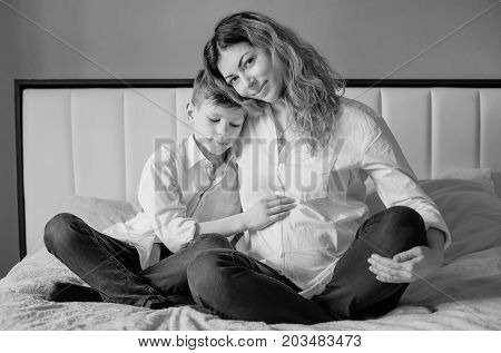 Happy son touches pregnant mother's belly sitting on the bed (Black and white)