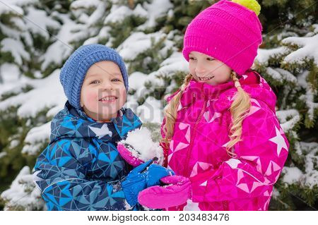 Two small happy children in a snow-covered forest. Playing with snow