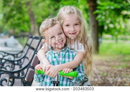 Two happy little children. The older sister hugs her younger brother in the park for a walk