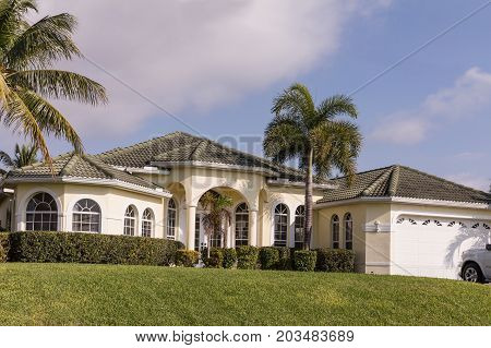 Typical Southwest Florida white concrete block and stucco home in the countryside with palm trees tropical plants and flowers grass lawn and pine trees. Florida. South Florida single family house