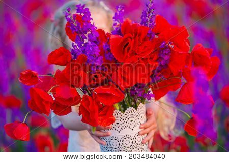 Small child holds a big beautiful bouquet with field poppies
