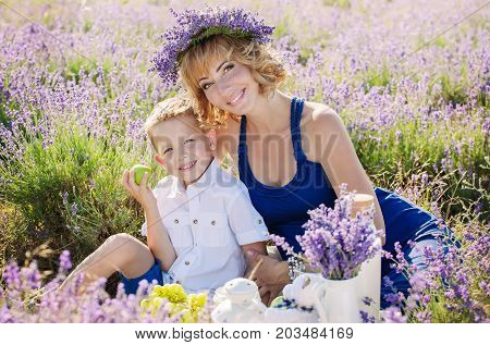 Happy small child hugs a pregnant mother on a picnic