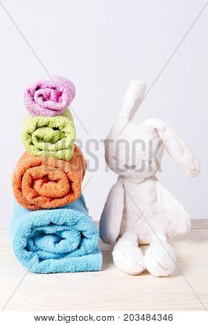 from small to large. towels stacked rolls. soft toy bunny on a wooden background