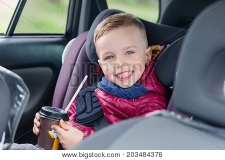Adorable toddler boy in safety car seat. Drinks cocoa