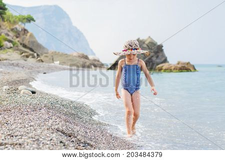 Adorable little girl walking along a pebble beach in swimsuit and hat