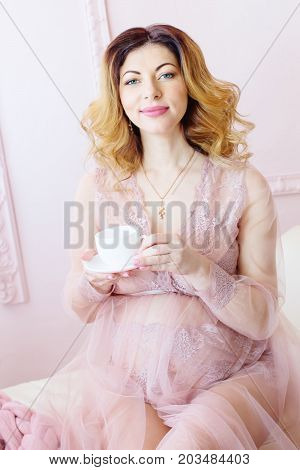 Pregnant woman with a cup in his hands on a light background