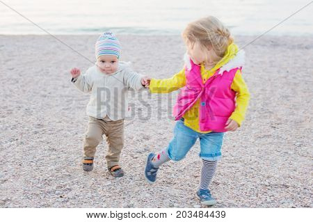 Little children older sister teaches brother to walk on the beach